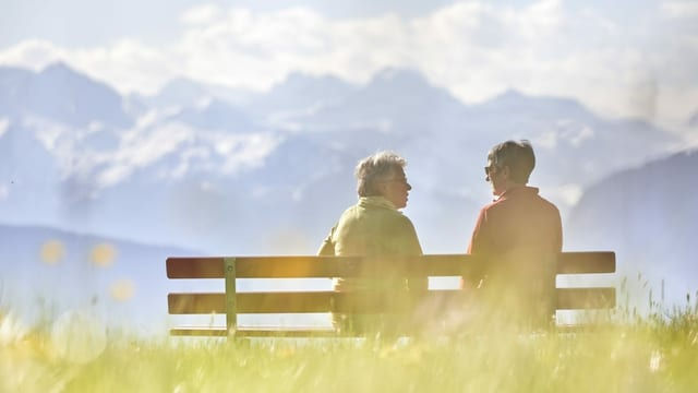 Zwei Frauen auf einer Bank vor einem Bergpanorama.
