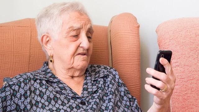 Eine ältere Frau schaut überfordert auf ihr Smartphone.