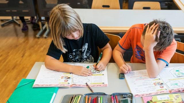 Zwei Schüler sitzen am Pult vor ihren Englisch-Heften.