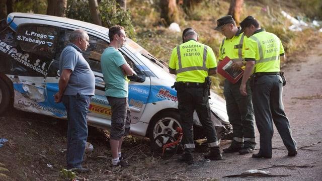 Polizisten begutachten ein demoliertes Rallyeauto.