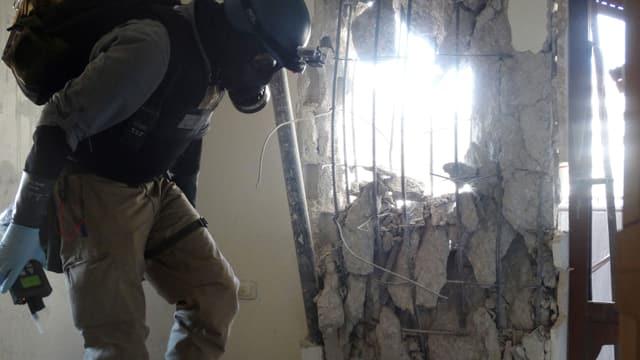 Ein Mann mit einer Gasmaske geht durch ein zerstörtes Haus.