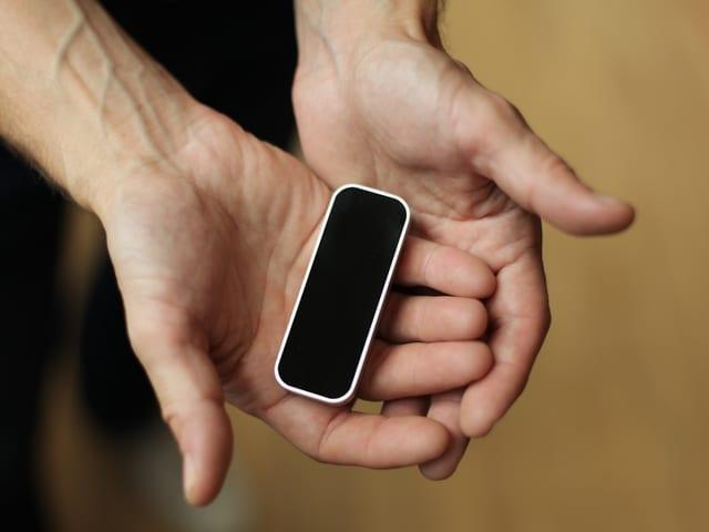 Zwei Hände halten ein kleines Kästchen, den Leap-Motion-Bewegungssensor