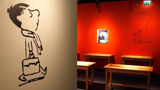 Die Comic-Figur des kleinen Nick mit Schal und Schultasche ist auf eine weisse Wand geklebt. Im Hintergrund ist in einem Raum eine Art Klassenzimmer aufgebaut, über deren Bänken weitere Bilder Sempés hängen.