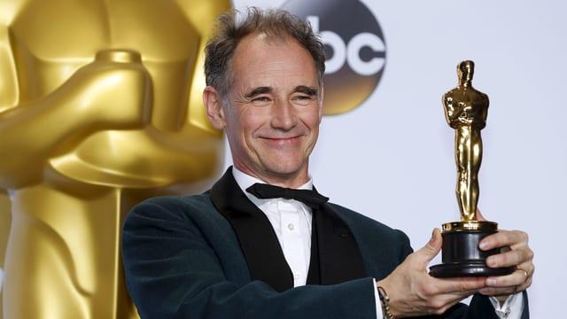 Mark Rylance hält freudestrahlend den Oscar in beiden Händen.