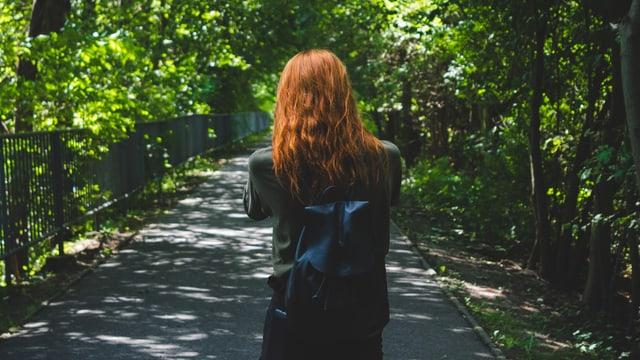 Eine Frau spaziert. Sie ist von hinten fotografiert. Sie hat rote Haare.