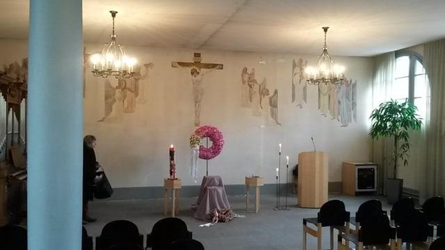 Abdankungshalle mit Kruzifix und anderen christlichen Symbolen an der Wand.