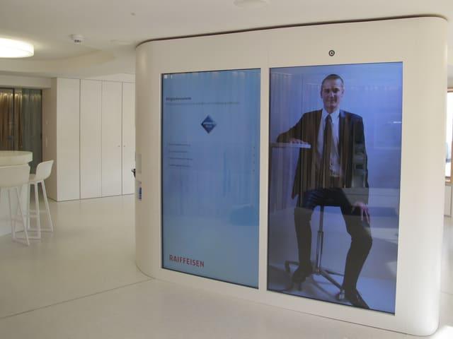 André Picard auf dem grossen Bildschirm in der Schalterhalle der Raiffeisenbank Alchenflüh