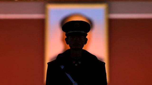 Soldat vor Mao-Plakat.