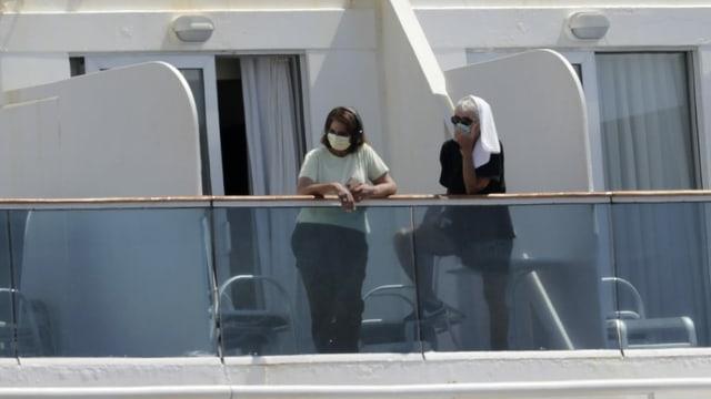 Zwei Frauen mit Gesichtmasken auf Balkon eines Schiffes.