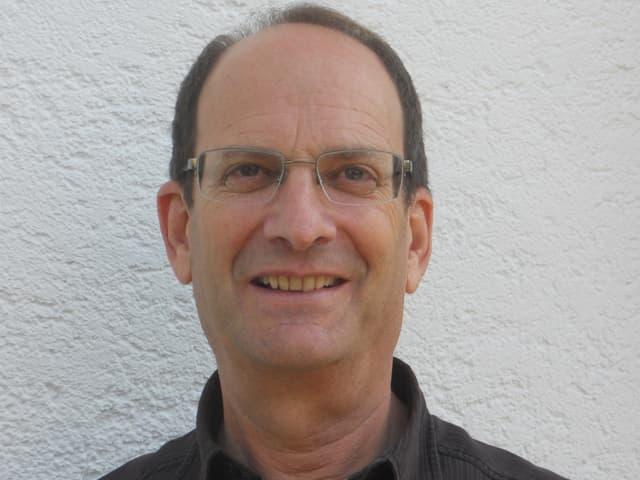 Peter Daniel mit Brille und schwarzem Hemd vor einer rauen Hausmauer.