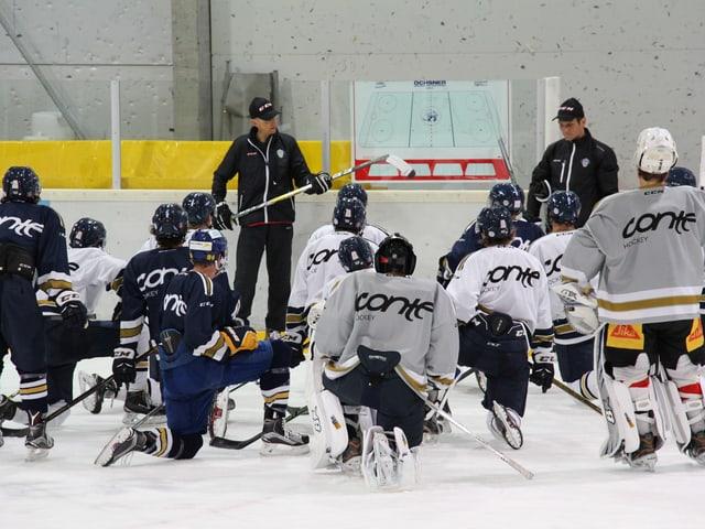 Eishockey-Spieler kauern vor ihren Trainern auf dem Eis.