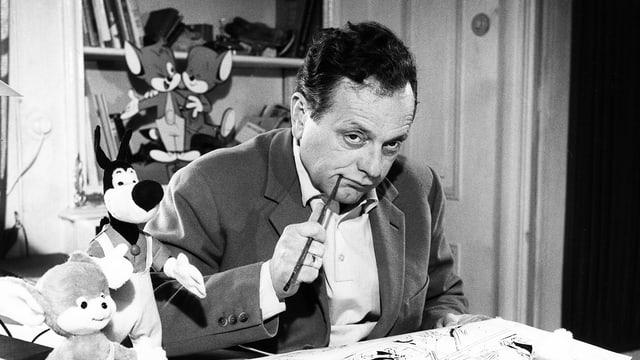 Ein Mann sitzt mit einem Stift in der Hand am Schreibtisch.