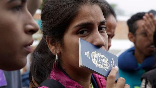 Eine Venezolanerin wartet mit ihrem Pass in der Hand