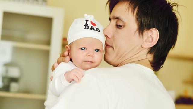 Mann hält Baby im Arm.