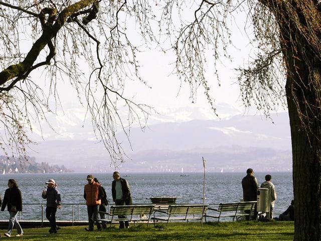 Ausfluegler spazieren am Sonntag, 11. Maerz 2007, bei Sonnenschein aber kaltem Wind am Ufer des Zuerichsees.
