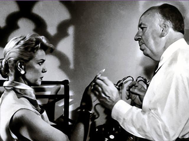 Hitchcock und Day diskutieren während Drehpause.