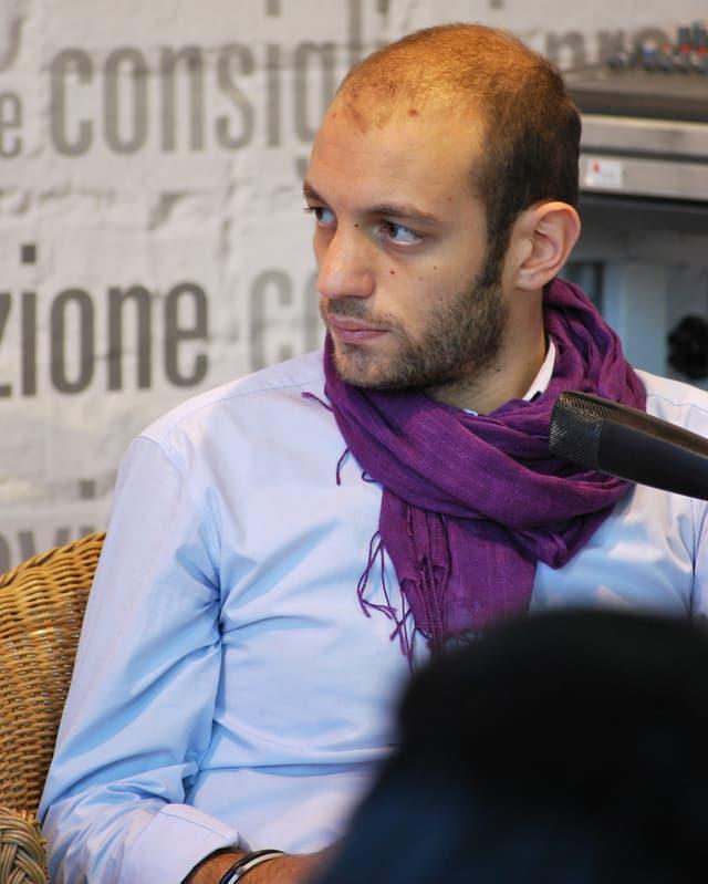 Giovanni Tiziano mit dem Blick von der Kamera abgewandt sitzt vor einem Mikrophon in einem Sessel.