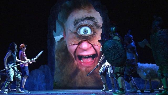 Eine Szene aus der Theateraufführung, ein riesiger Zyklopenkopf und Männer die sich vor ihm fürchten.