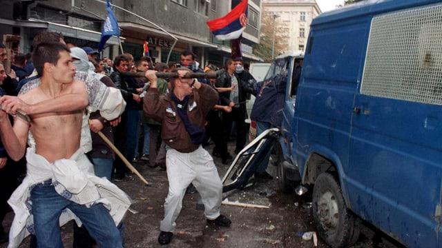 Ein Polizeifahrzeug wird von bewaffneten Demonstranten attackiert.