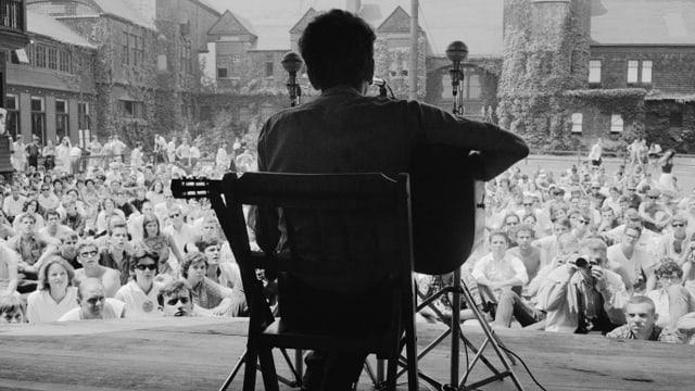Mann mit Gitarre vor grossem Publikum