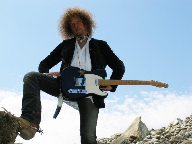 Aufnahme aus der Froschperspektive: Luke Gasser steht inmitten einer steinigen Landschaft, er trägt Cowboystiefel und seine Gitarre.