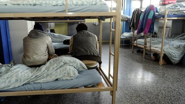 Zwei Männer sitzen auf einem Etagenbett.