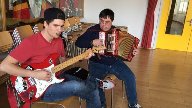 Ein junger Mann spielt Gitarre, daneben ein anderer Mann an der Handorgel.