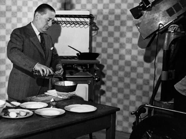 Schwarz-weiss-Aufnahme eines Mannes in Anzug, der vor einer Kamera kocht.