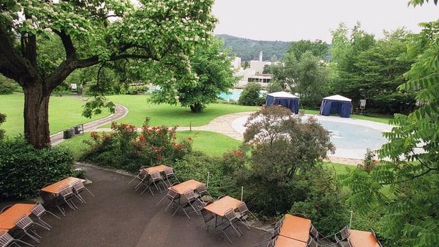 Kinderbecken in einem Freibad inmitten von Bäumen, davor Tische und Stühle eines Restaurants.