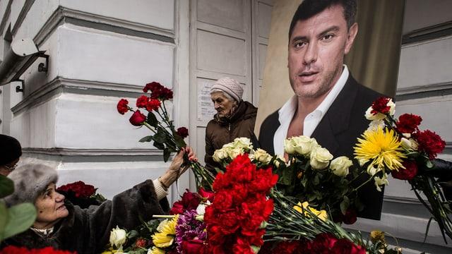 Frau legt Rosen nieder vor einem Bild Boris Nemzows