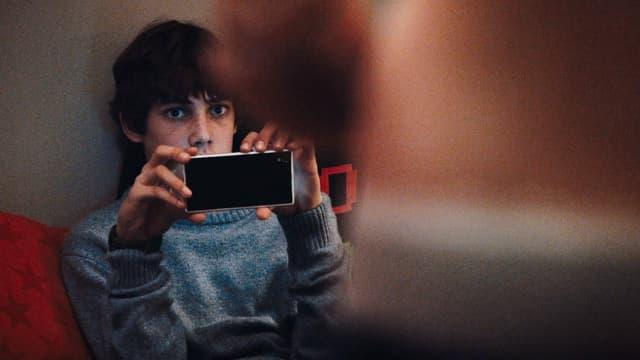 Ein Junge filmt mit dem Handy eine junge Frau.