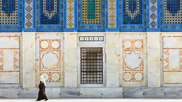 Eine Frau vor einer Moschee