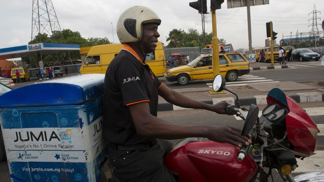 Ein Jumia-Mitarbeiter liefert Ware aus auf einem Motorrad.