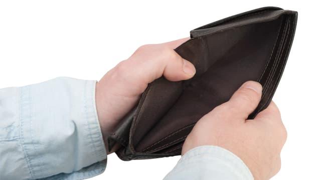 Zwei männliche Hände halten ein Portemonnaie und präsentieren das leere Geldscheinabteil.