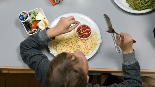 Ein Kind beim Spaghettiessen an einer Zürcher Tagesschule.