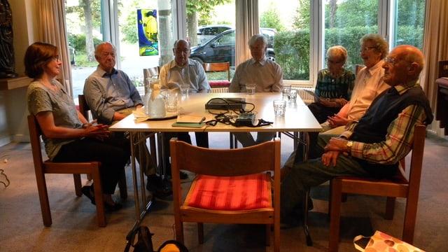 Seniorinnen und Senioren sowie eine Betreuerin sitzen in einer Gesprächsrunde an einem Tisch.