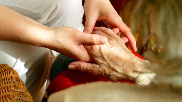 Die Hand einer Pflegerin greift nach der Hand einer alten Frau.