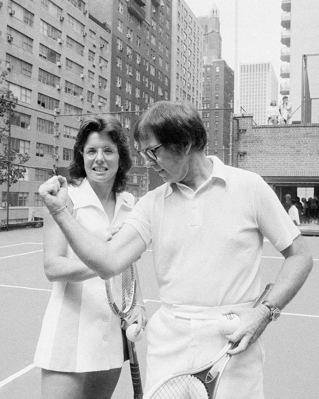 Billie Jean King greift auf dem Tennisplatz nach Bobby Riggs Bizeps.