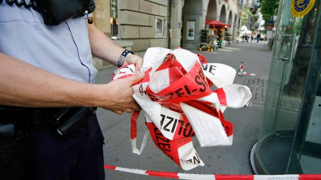 Ein Polizist entfernt nach einer Bombendrohung an der Zürcher Bahnhofstrasse das Absperrband.