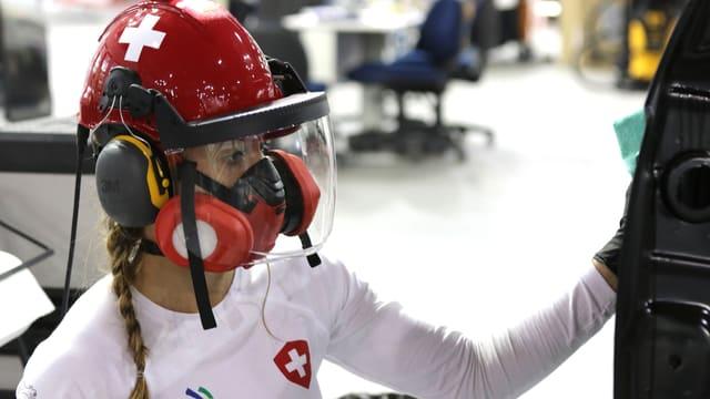 Eine Frau mit rotem Helm, Ohrschützern und Atemmaske in weissem T-Shirt arbeitet an einer Autotür.