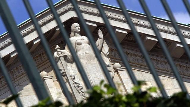Justizia im Gibel des Bundesgerichtsgebäudes, fotografiert durch einen Gitterzaun
