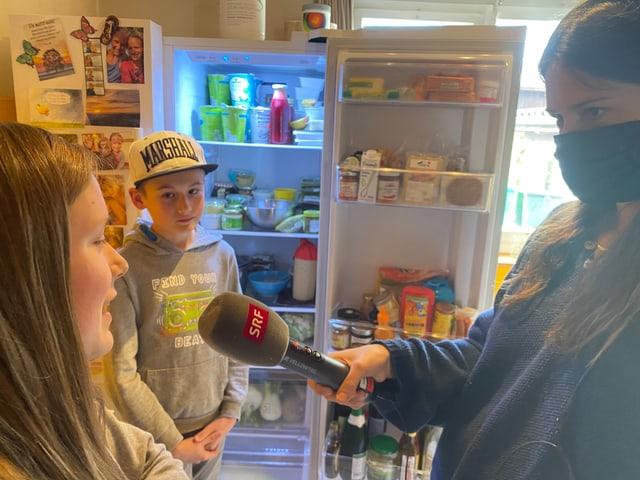 Muriel und Gianluca stehen mit Dania vor dem Kühlschrank.