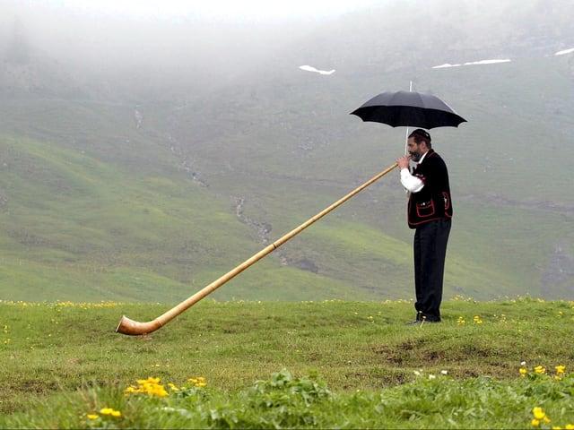 Ein Älpler bläst sein Alphorn auf einer Maiensäss unter einem Schirm. Der Talkessel ist wolkenverhangen.