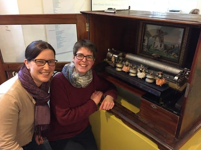 Zwei Frauen neben einem historischen Musikautomaten