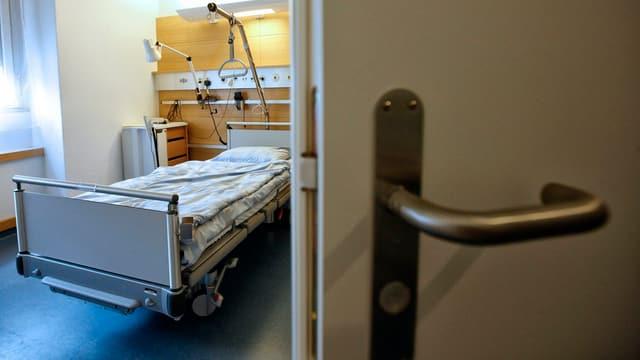 Blick in ein leeres Spitalzimmer durch eine halb geöffnete Tür.