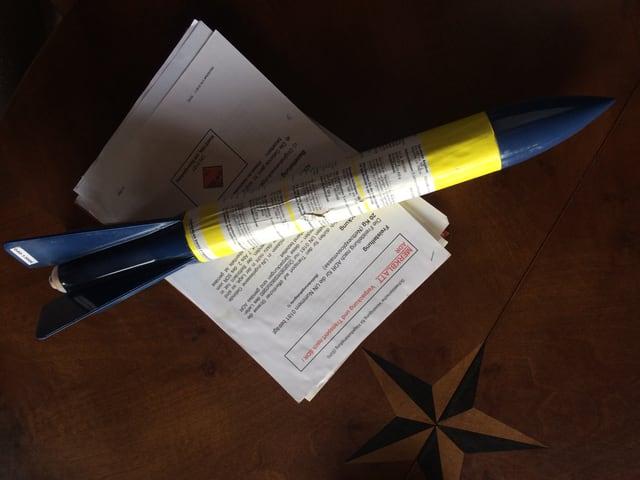 """Blau-Gelbe Rakette liegt auf Blättern mit Aufschrift """"Merkblatt"""", darunter Holztisch"""