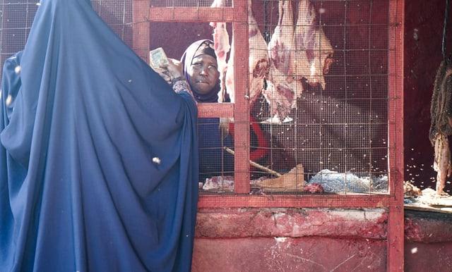 Eine Frau sitzt hinter einem Gitter und verkauft Fleisch.