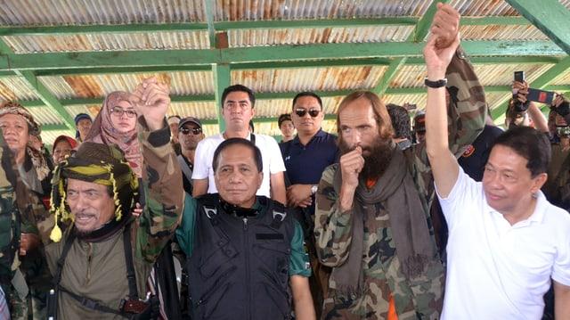 Mehrere Männer stehen nebeneinander, sie recken die Hände in die Höhe.