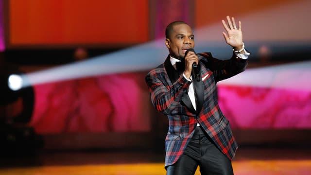 Ein Mann steht im Anzug auf der Bühne. Er singt in ein Mikrofon und hält seine linke Hand hoch.
