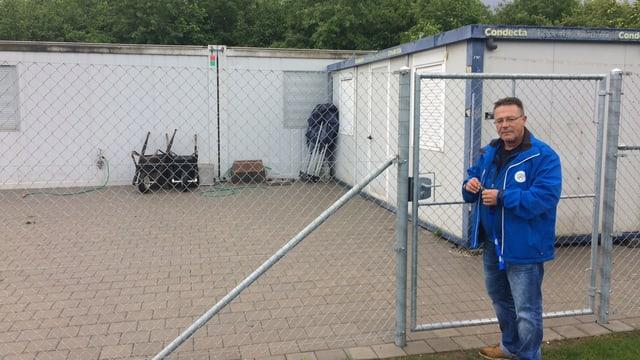 Mann öffnet ein Gitter. Im Hintergrund ist eine Container-Siedlung zu erkennen.